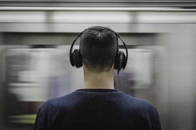 man commuting with headphone on